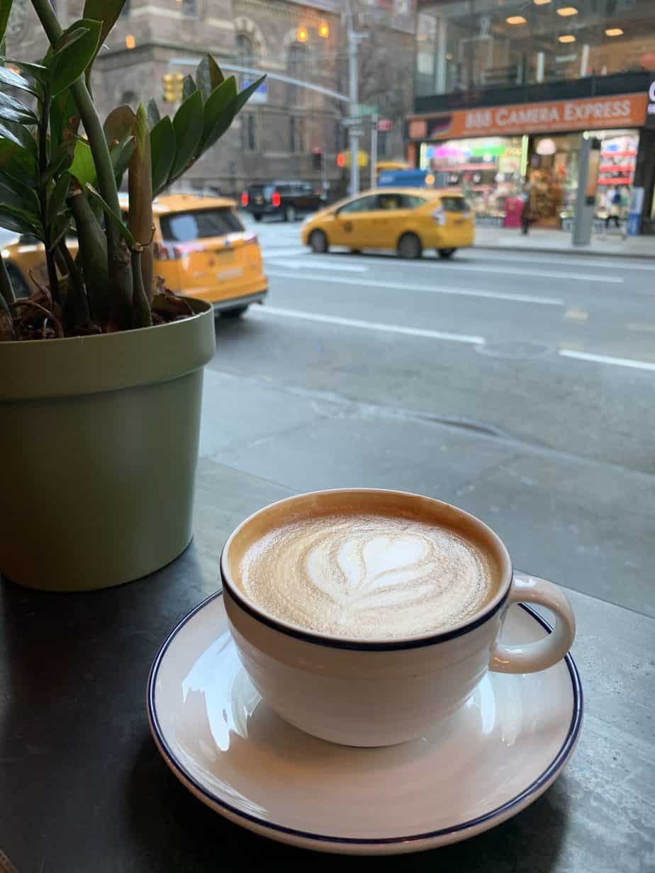A cup of coffee with yellow taxis in the background