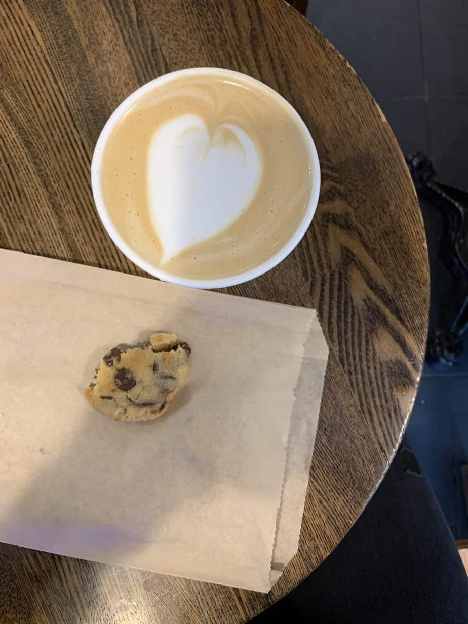 A cup of coffee with a half eaten chocolate chip cookie