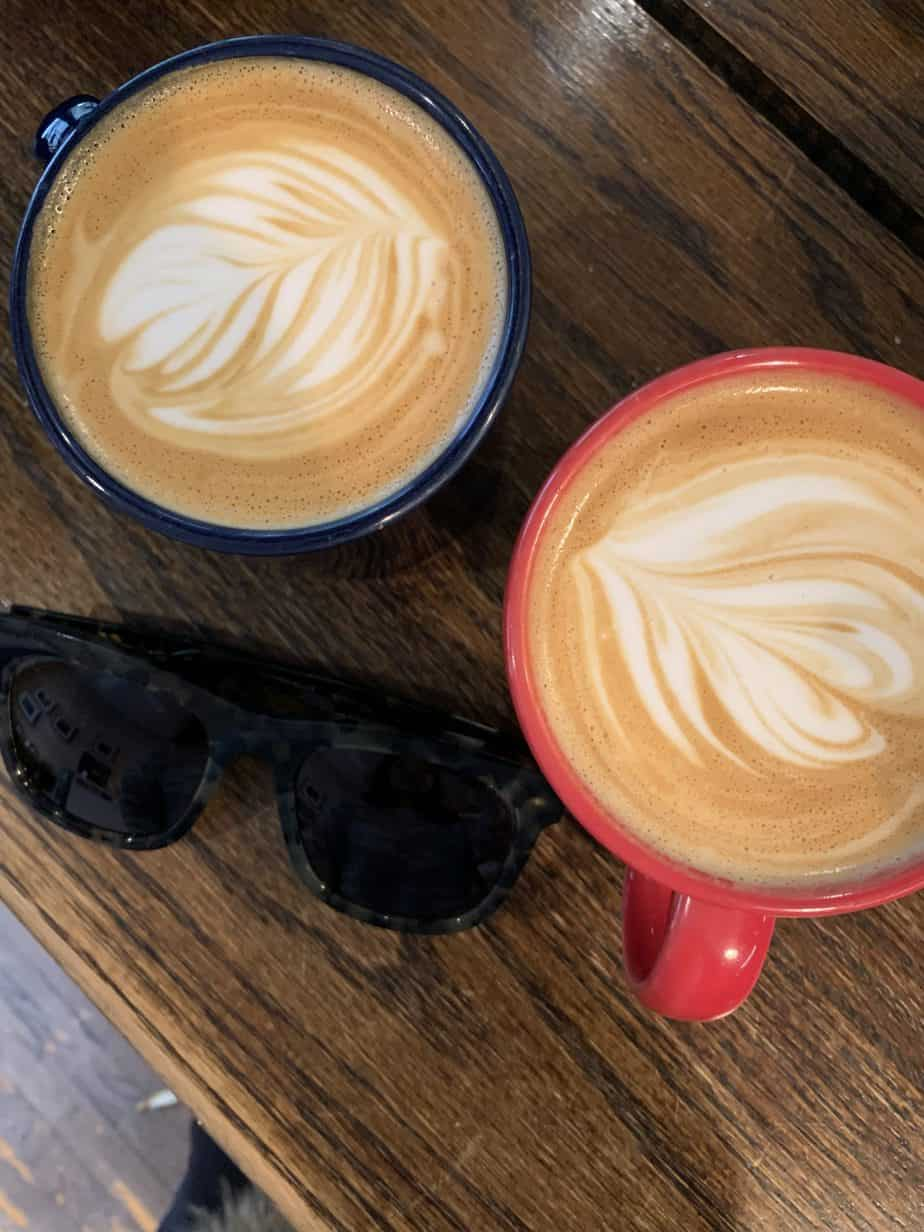 Two coffee mugs with coffee art and sunglasses