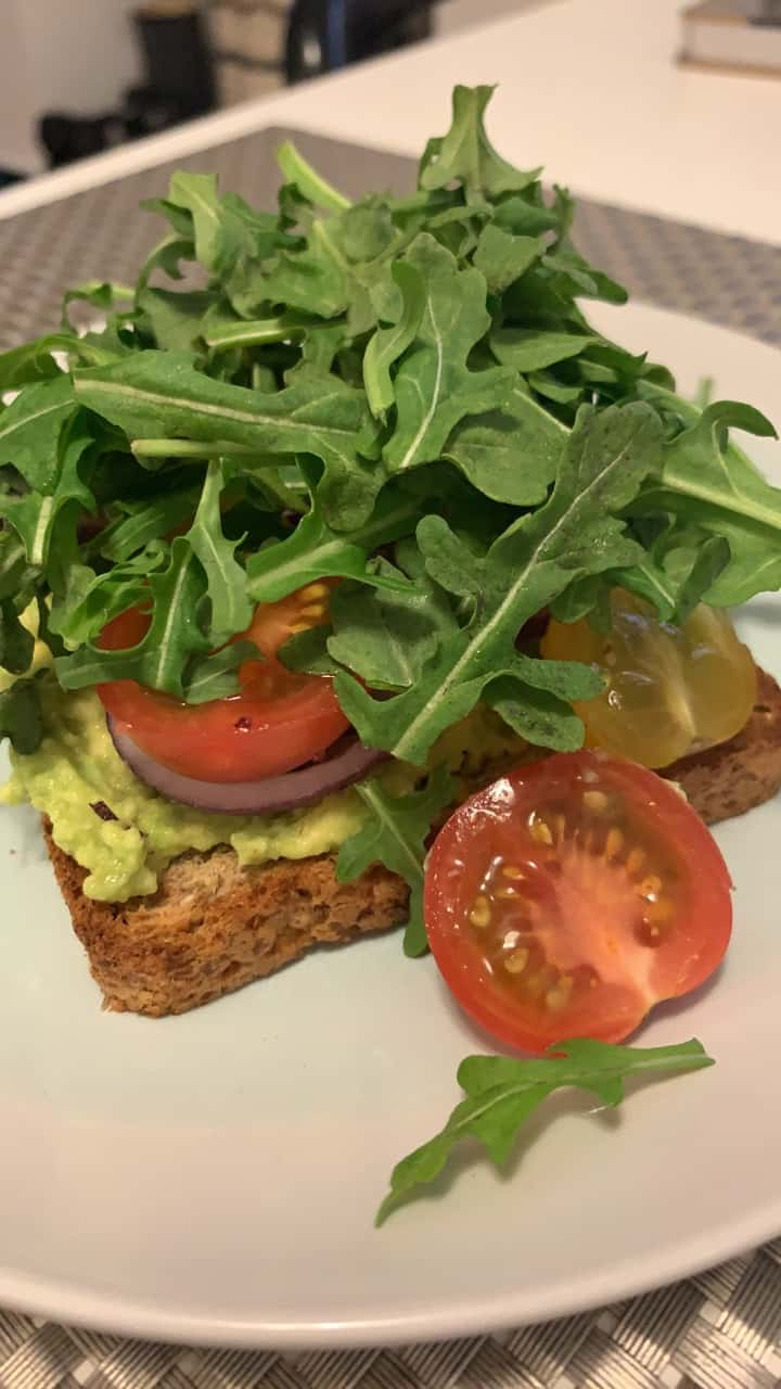 Arugula on a smashed avocado toast with cherry tomatoes and red onions