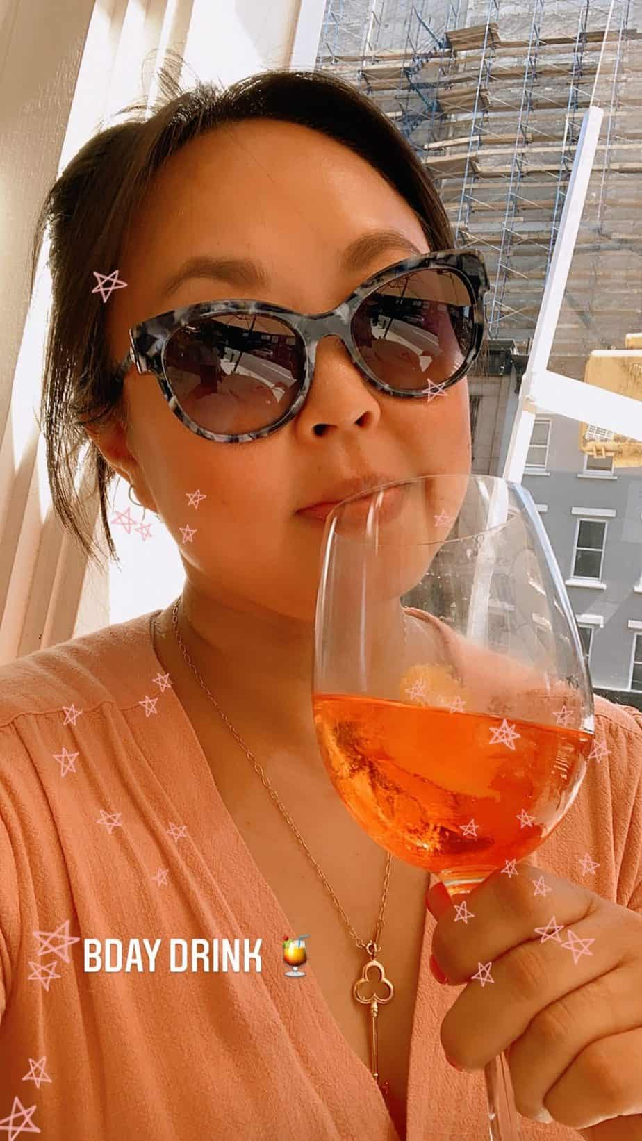 Girl in sunglasses holding an aperol spritz