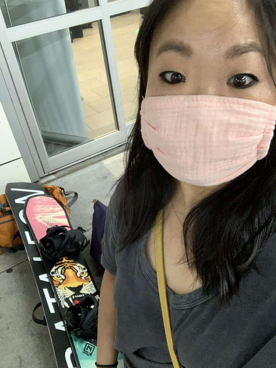 Asian girl with pink mask with snowboards in the background