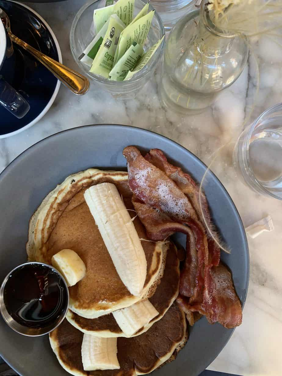 Blue plate with bananas bacon and pancakes